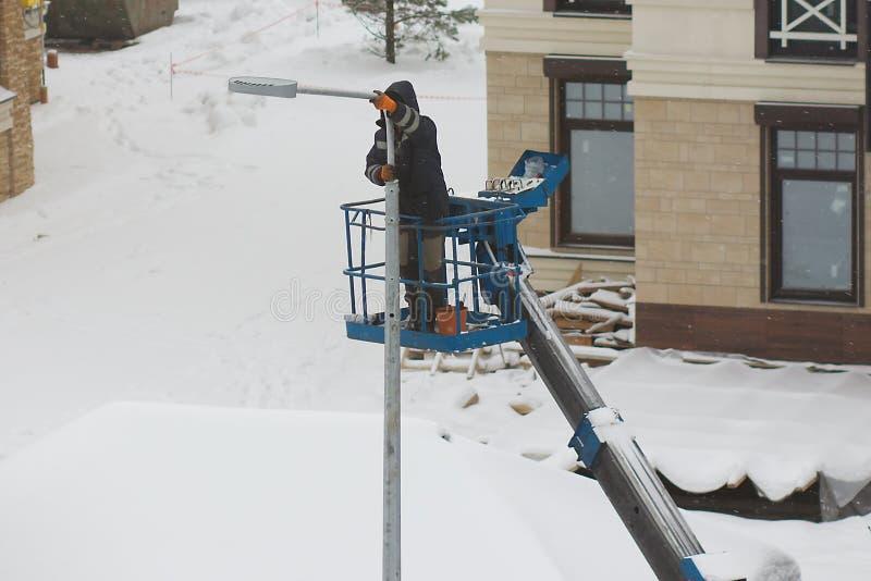 En arbetare installerar ett lyktaljus royaltyfri foto