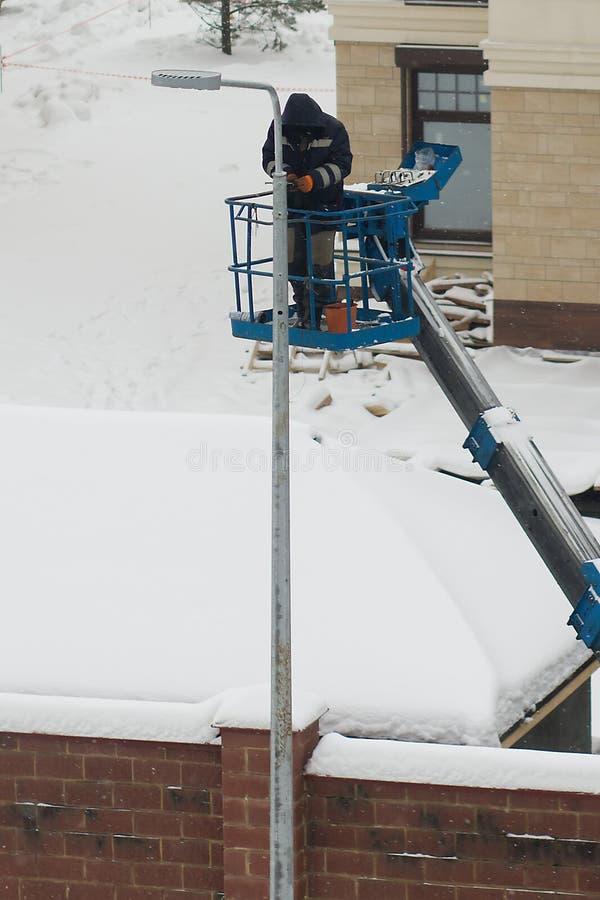 En arbetare installerar ett lyktaljus arkivbild