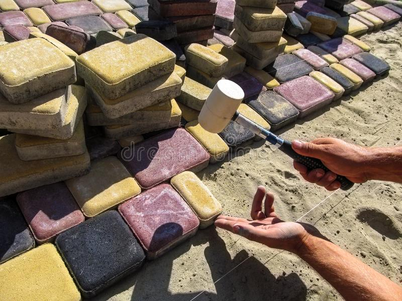 En arbetare installerar ` för stad för trottoartegelplatta` gammal, arkivfoton