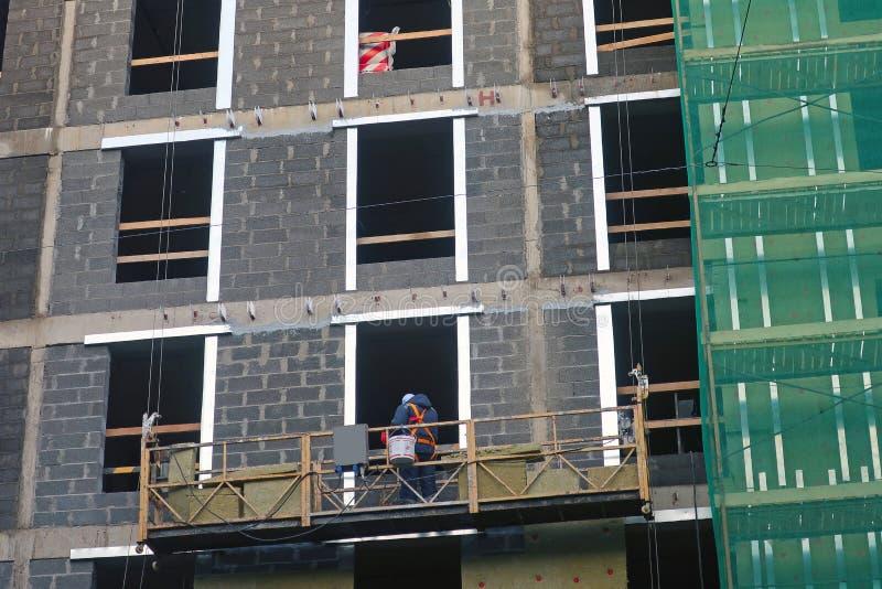 En arbetare installerar värmeisolering på väggen av en nybygge arkivbilder