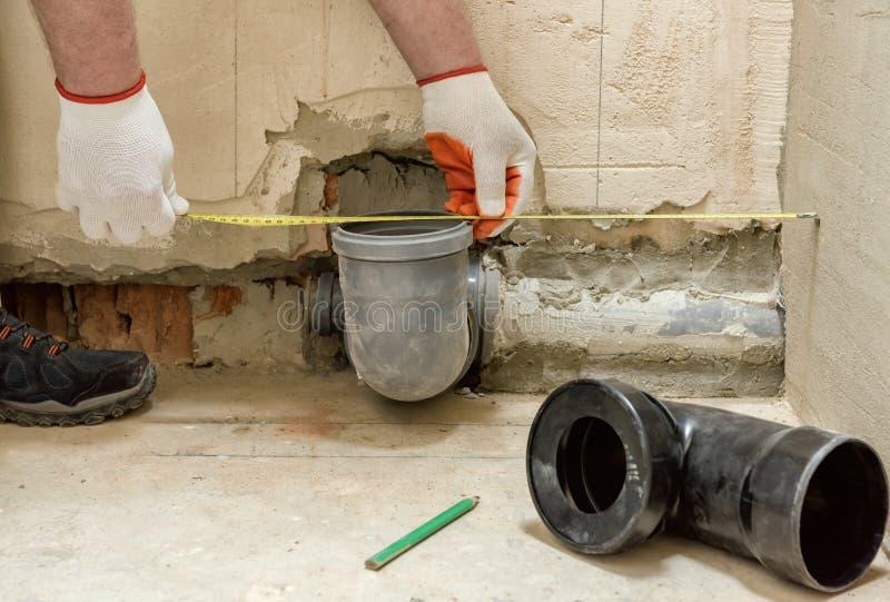 En arbetare m?ter kloakavrinningr?ret royaltyfri bild