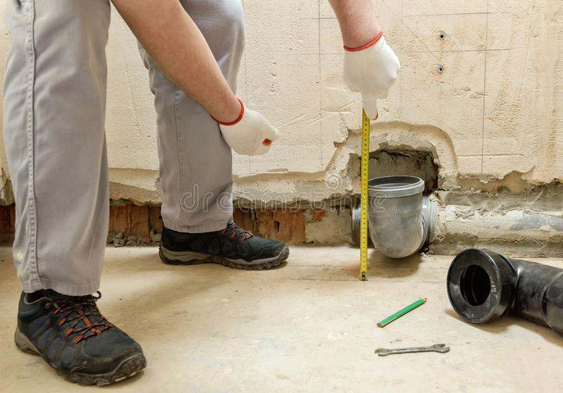 En arbetare m?ter kloakavrinningr?ret royaltyfria foton