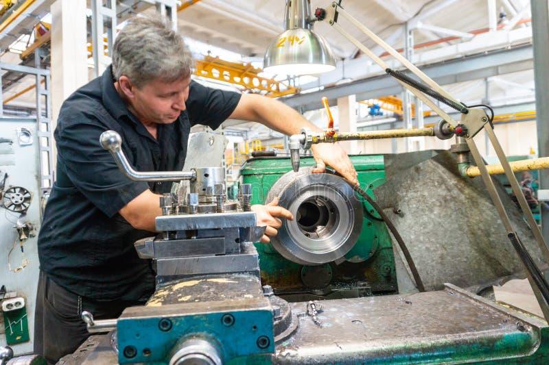 En arbetare, en man i en svart skjorta och säkerhetsexponeringsglas, kontrollerar delen för lämplighet för bruk i utrustning Rote royaltyfri foto