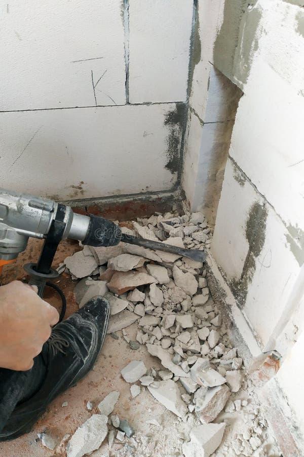 En arbetare med en hålapparat bryter väggen och fundamentet av huset för att föra elektriska trådar arkivbilder