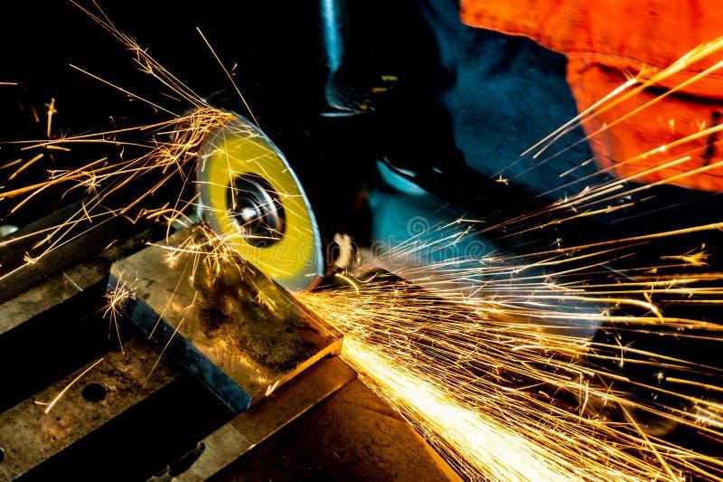 En arbetare sågar ett metallmellanrum med ett bitande hjul med en malande maskin, stora gnistor flyger omkring royaltyfri fotografi