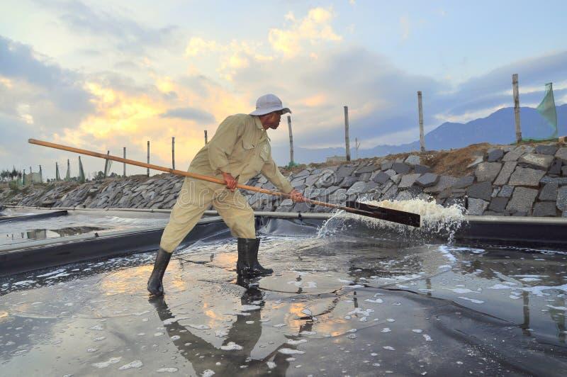 En arbetare smäller vatten ut ur det salta dragande ut fältet i ottan arkivfoton
