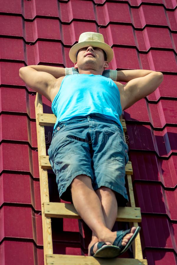 En arbetare tar ett solbad på taket av huset royaltyfri bild