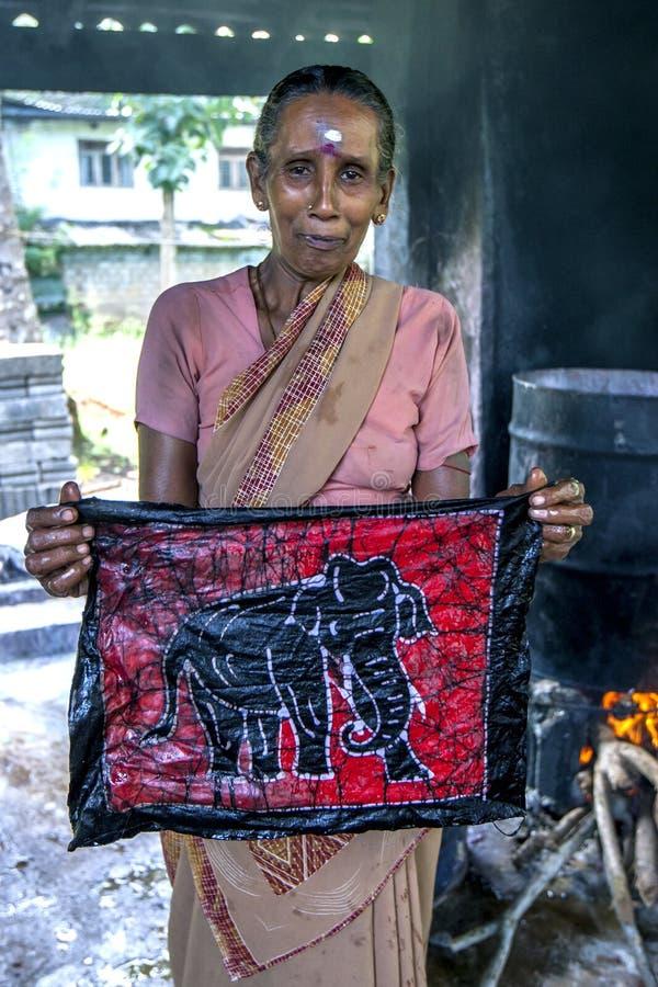 En arbetare visar en batik på den Baba Batik fabriken i Matale i Sri Lanka arkivfoton