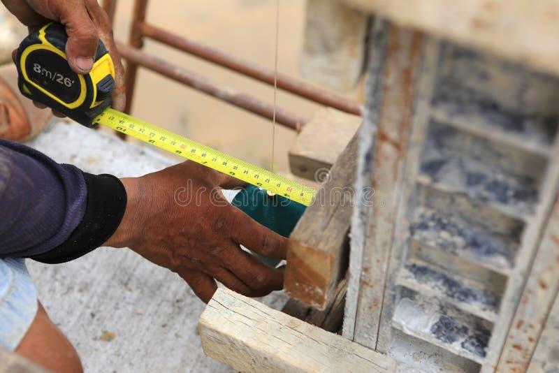 En arbets- man som använder en blylod för kontroll arkivbild
