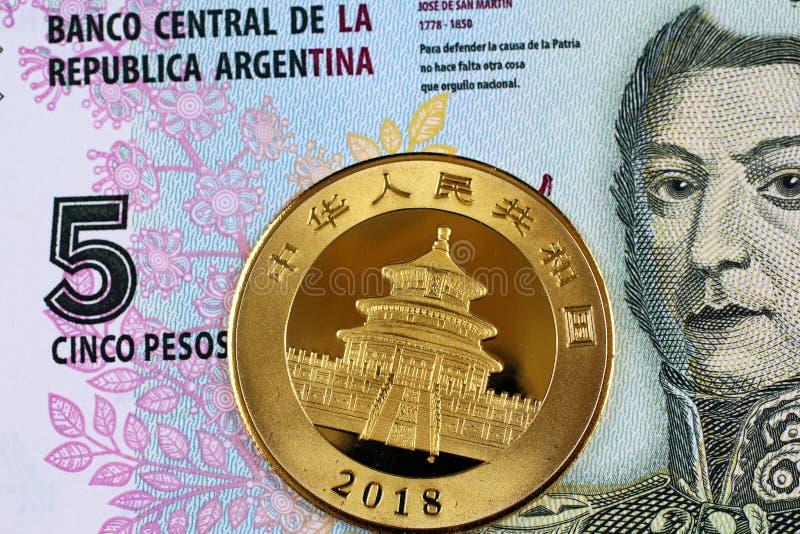 En argentinsk fem peso räkning med ett kinesiskt ett guld- mynt för uns royaltyfria bilder