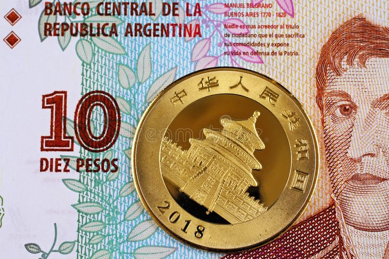 En argentinsk tio peso räkning med ett kinesiskt ett guld- mynt för uns arkivfoto