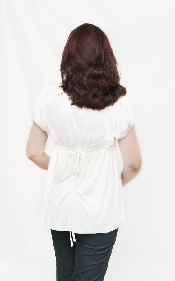 En arrière de la fille dans un chemisier blanc image stock