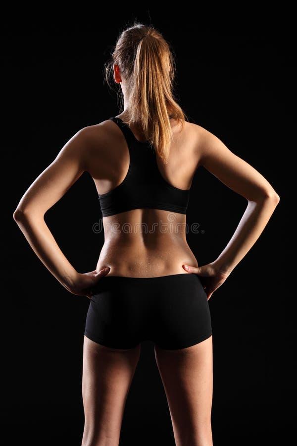En arrière de la jeune femme d'ajustement dans l'équipement noir de sports image stock