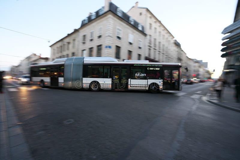 En artikulerad buss eller en bendy buss på hörnet av den Stanislas gatan och D400 i aftonen i Nancy royaltyfri fotografi