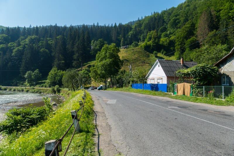 En asfaltväg i ett bergsområde med lantliga hus på en sida och ett damm på annan arkivfoton