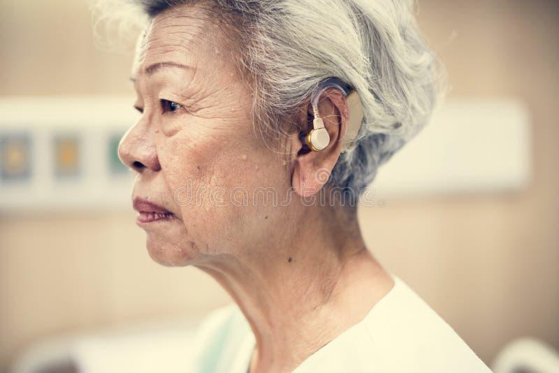 En asiatisk äldre kvinna med hörapparat royaltyfria bilder
