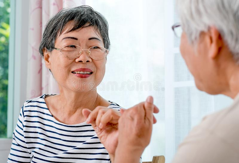 En asiatisk äldre kvinnakrok varje andra lillfinger till annan med att le framme av balkongen i huset royaltyfria foton