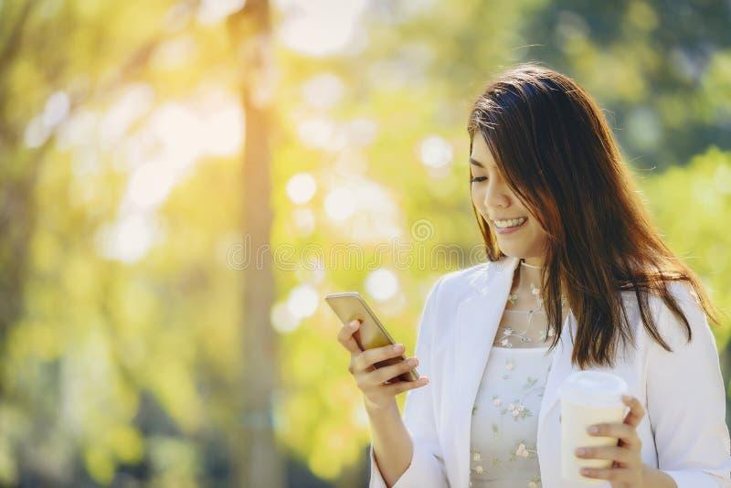 En asiatisk affärskvinna är avslappnande med hennes smartphone och coff arkivbild