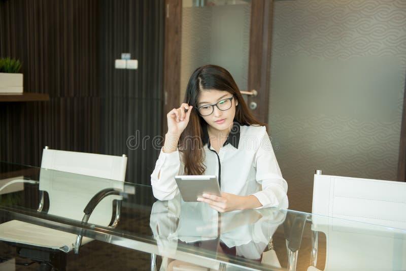 En asiatisk affärskvinna som i regeringsställning använder en minnestavla royaltyfria foton