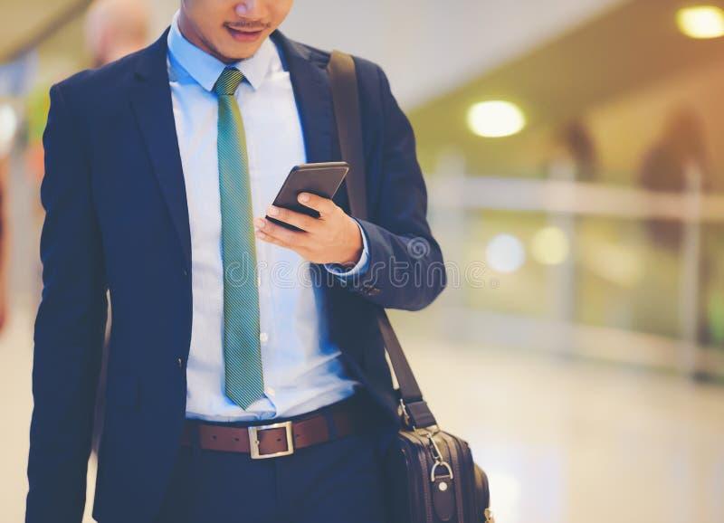 En asiatisk affärsman använder en smartphone för att få i affärswh royaltyfri foto