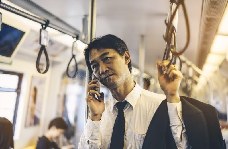 En asiatisk affärsman går tillbaka hem med en trött dag i en bar arkivfoton