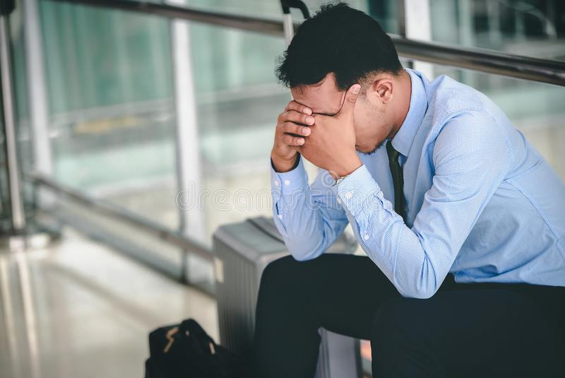 En asiatisk aff?rsman sitter p? hans bagage Han var stressad och sedd hans smartphone p? flygplatsen royaltyfri fotografi