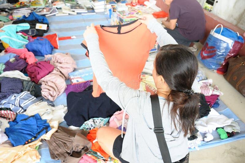 En asiatisk dam som upp väljer ett stycke av kläder på en fri marknad fotografering för bildbyråer