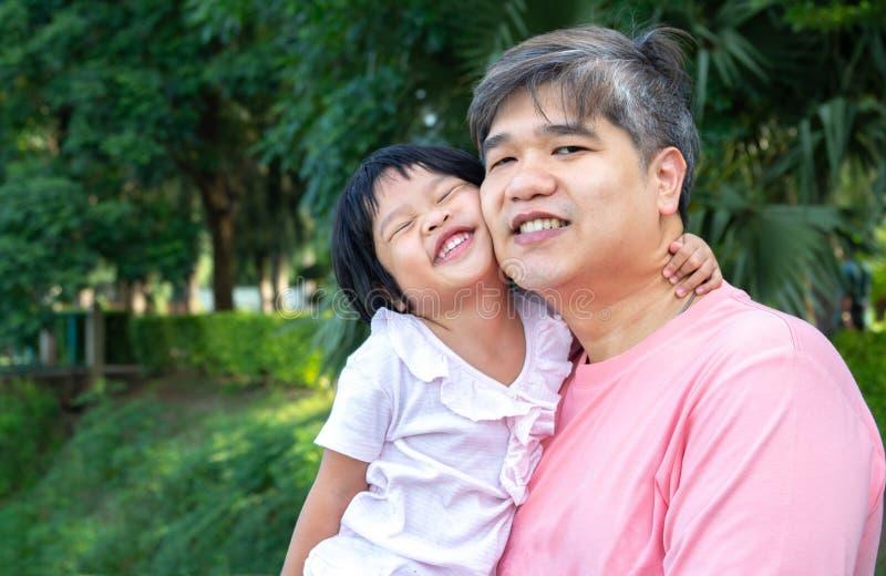 En asiatisk fader b?r en ?lskv?rd dotter till hennes br?stkorg b?de fadern, och dottern log lyckligt Asien familj och att ?lska c fotografering för bildbyråer