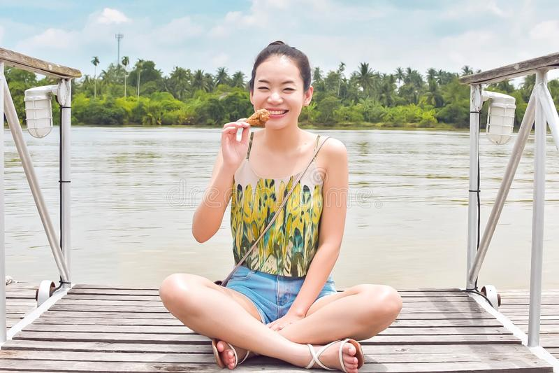 En asiatisk härlig kvinna är att ta vilar bredvid floden royaltyfri fotografi