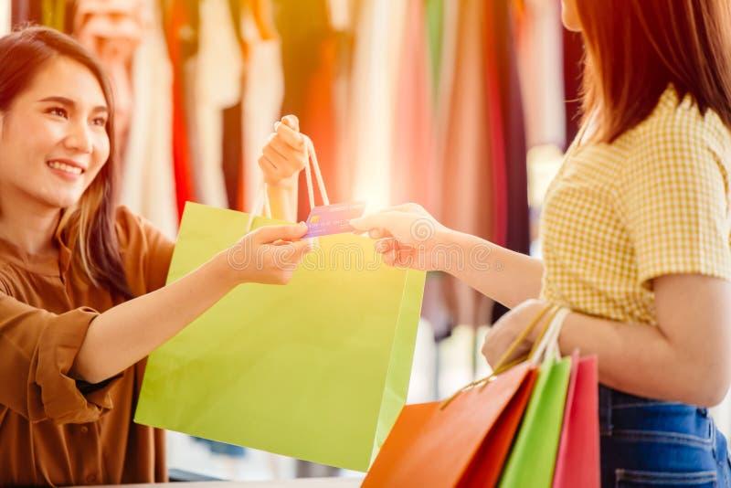 En asiatisk kvinna gillar att handla med kreditkort för att betala för att köpa många försäljningsartiklar och ett kort som affär arkivbilder