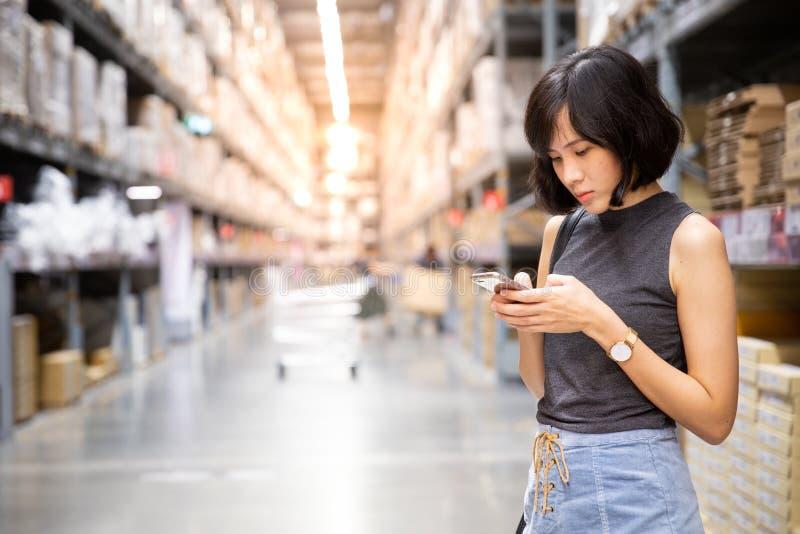 En asiatisk kvinna som gör att shoppa direktanslutet via mobiltelefonen i kriget arkivbilder