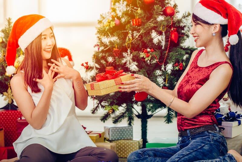 En asiatisk kvinna som ger sin vän en ny julklapp med en gåva. arkivbilder