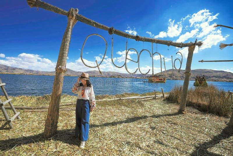En asiatisk kvinnlig tar foto på sjön Titicaca, en stor djup sjö i Anderna på gränsen av Bolivia och Peru arkivfoto
