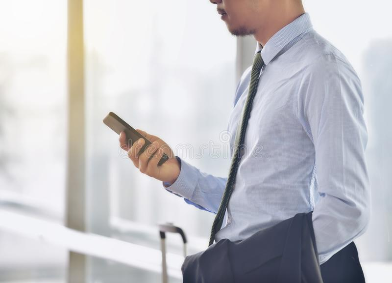 En asiatisk manlig entreprenör använder en mer smart telefon till communicaen royaltyfri bild