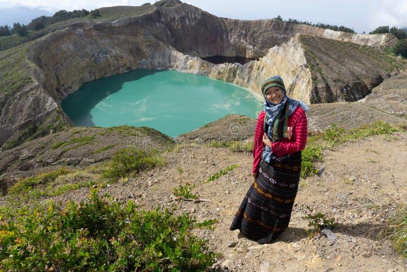 En asiatisk muslimsk kvinna som bär en hijab, tar ett foto framme av en grön sikt av Kelimutu-Flores sjön royaltyfri foto