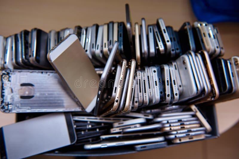 En ask med mycket brutna mobiltelefoner arkivbild