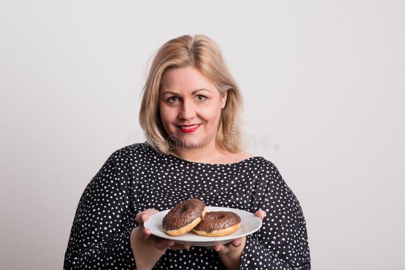 En attraktiv överviktig kvinna i studion, hållande donuts på en platta royaltyfri foto