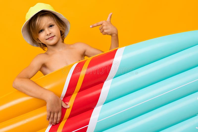 En attraktiv europeisk blond pojke i ett sommarpanama med en uppblåsbar badmadrass på en orange bakgrund royaltyfri bild