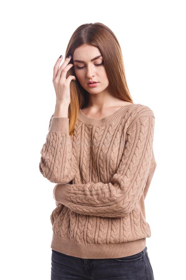 En attraktiv flicka med mörkt hår rymmer hennes hand nära framsidan och ser ner isolerat arkivbilder