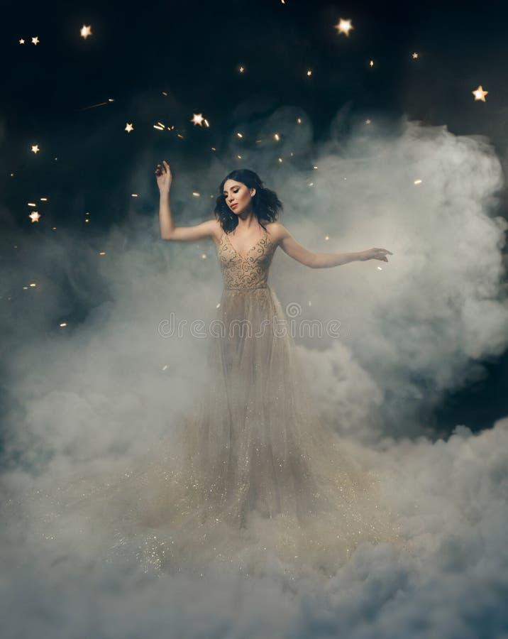 En attraktiv gudinna står i molnen i ett lyxigt, guld-, brusandeklänningen Nyckfull frisyr Mot royaltyfri bild
