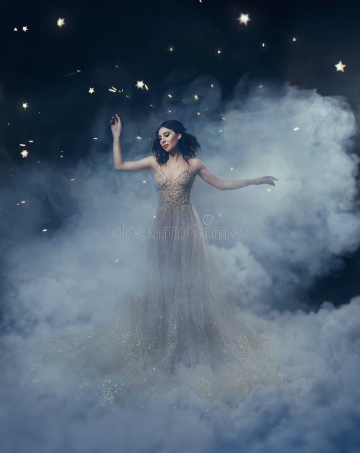 En attraktiv gudinna står i molnen i ett lyxigt, guld-, brusandeklänningen Nyckfull frisyr Mot royaltyfri fotografi