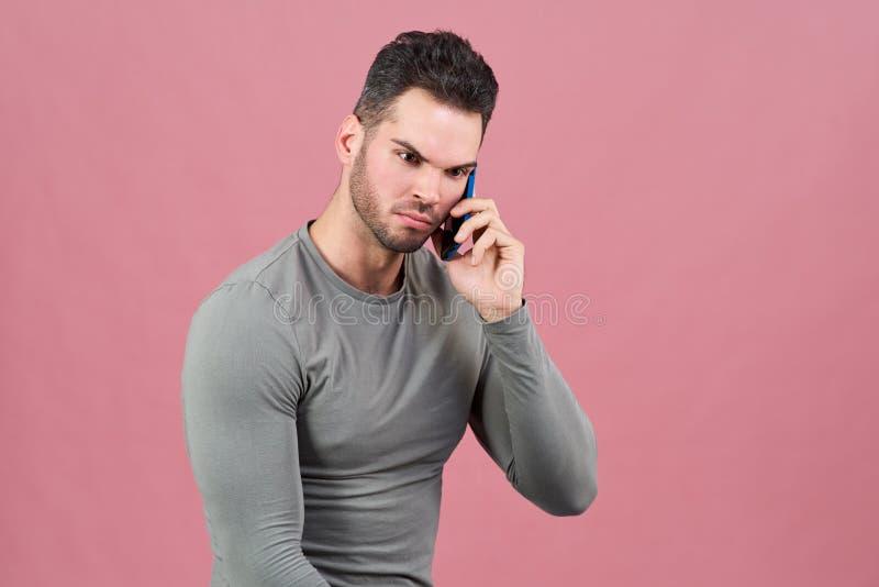 En attraktiv idrotts- man rynkar pannan hans ögonbryn, när han talar på telefonen Dåliga nyheter kommunikationsproblem royaltyfri bild