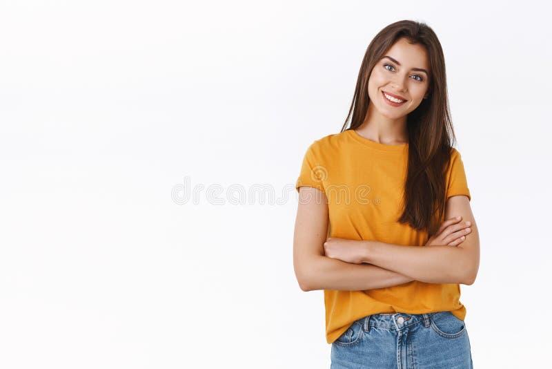 En attraktiv kvinna i gula t-shirthandtag över bröstet med självsäkert, nöjt uttryck, lutande huvud och leende. royaltyfria foton