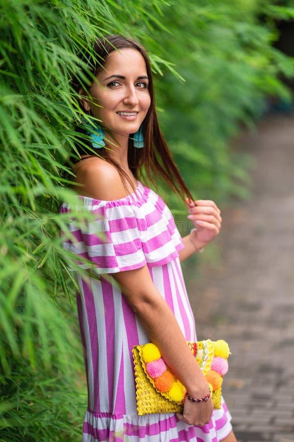 En attraktiv kvinna i en randig klänning och en handväska i hennes händer lutade mot ett grönt staket arkivbild