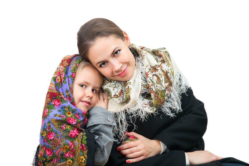 En attraktiv kvinna med lilla flickan i rysssjaletter royaltyfri foto