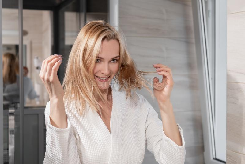 En attraktiv medelålders blond kvinna i ett vitt lag står framme av en spegel i badrummet Handlaghår med arkivbilder