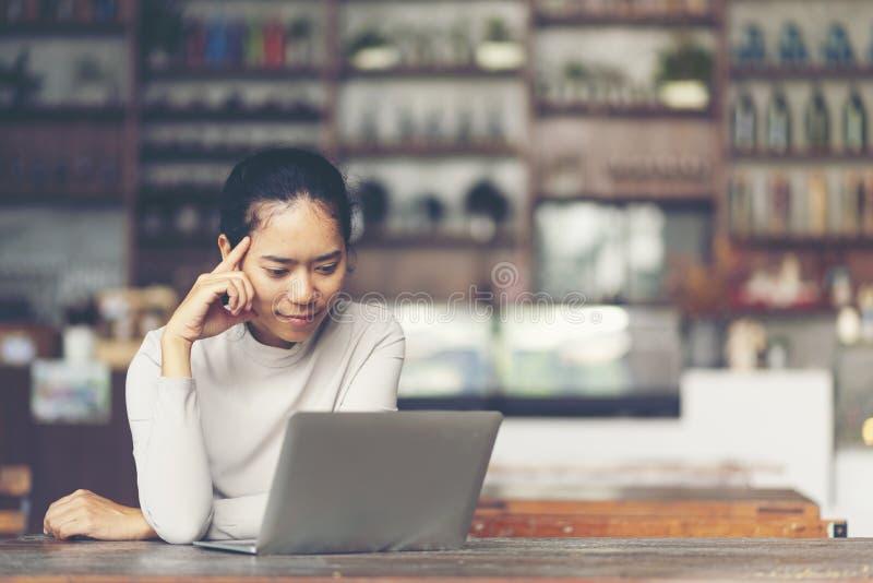 En attraktiv mitt åldrades affärskvinnan som framme sitter av lapt arkivbilder