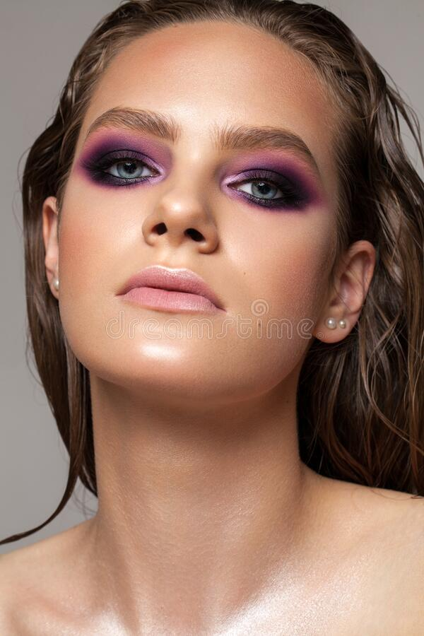 En attraktiv sexig flicka med professionell kvällsssmink, perfekt skuggande hud, vått hår och trendiga lila rökiga ögon royaltyfri bild