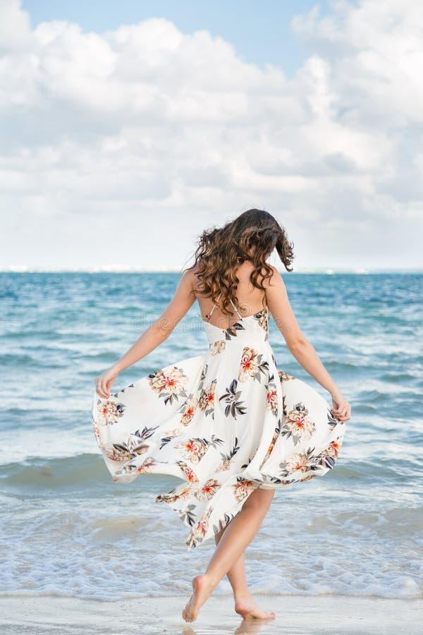 En attraktiv ung brunettkvinna i en vit sommarklänning på en strand i Mexico royaltyfri foto