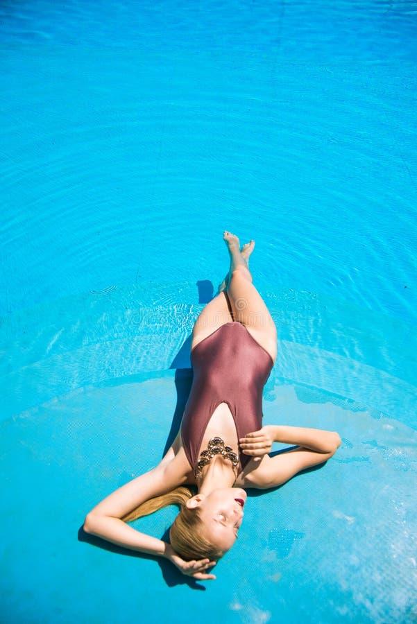 En attraktiv ung flicka med blond hår med en perfekt figur i en trendisk bikini i den utomhuspoolen på sommaren arkivbild